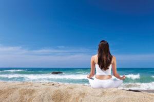 Mindfulness - Mediterende kvinde på strand